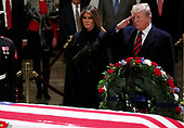 U.S. President Donald Trump salutes as he stands with First Lady Melania Trump at the flag draped casket of former U.S. President George H.W. Bush as it lies in state inside the U.S. Capitol Rotunda on Capitol Hill in Washington, U.S., December 3, 2018. REUTERS/Jonathan Ernst/Pool