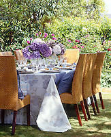 Table laid for summer lunch decorated with purple hydrangeas and linen