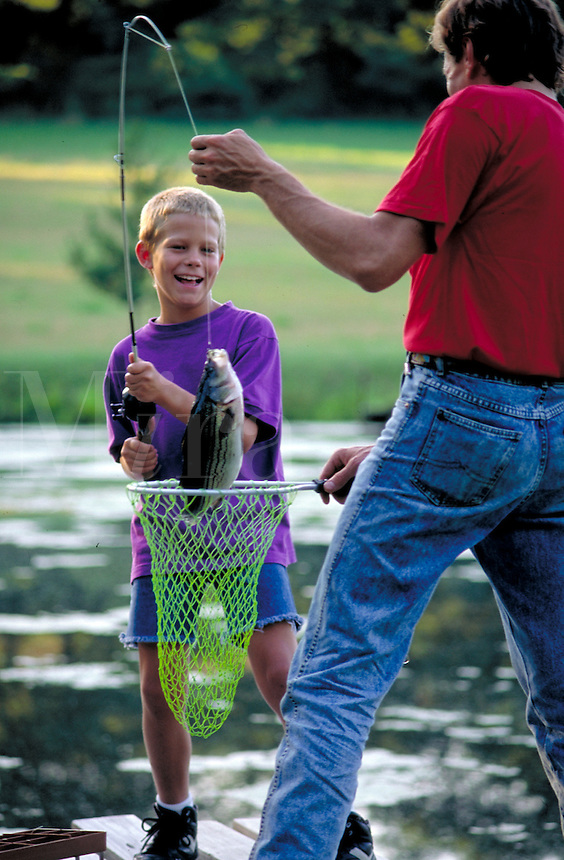 Boy about 9 years old is proud of large fish catch as his father, hold the net for him. father and son. York Pennsylvania United States Farm pond.