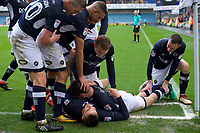 Lee Gregory of Millwall (bottom) is mobbed by his team mates after scoring his side's 2nd goal to make not 2-0 during the Sky Bet Championship match between Millwall and Nottingham Forest at The Den, London, England on 30 March 2018. Photo by Alan  Stanford / PRiME Media Images.