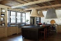 The contemporary kitchen continues the wood-clad decorative theme of the property with a ceiling of rough-hewn planking