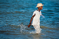 A young Candomblé devotee wades in the sea during the ritual procession in honor to Yemanjá, the goddess of the sea, in Amoreiras, Bahia, Brazil, 3 February 2012. Yemanjá, originally from the ancient Yoruba mythology, is one of the most popular ?orixás?, the deities from the Afro-Brazilian religion of Candomblé. Every year on February 3rd, hundreds of Yemanjá devotees participate in a colorful celebration in her honor. Faithful, usually dressed in the traditional white, gather at the beach on Itaparica island to leave offerings for their goddess. Gifts for Yemanjá include flowers, perfumes or jewelry. Dancing in the circle and singing ancestral Yoruba prayers, sometimes the followers enter into a trance and become possessed by the spirits. Although Yemanjá is widely worshipped throughout Latin America, including south of Brazil, Uruguay, Cuba or Haiti, the most popular cult is maintained in Bahia, Brazil.