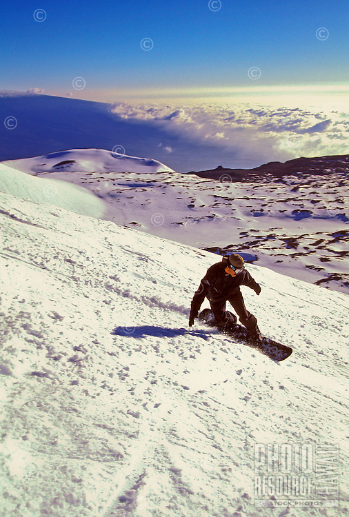 A snowboarder races down the snowy slopes of Mauna Kea on the Big Island of Hawaii, with white clouds merging with the snow in the background.