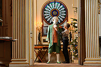 """BNPS.co.uk (01202 558833)<br /> Pic: ZacharyCulpin/BNPS<br /> <br /> Denise applies the finishing touches to a footman's costume at Uppark <br /> <br /> Ori-garments -  Artist Denise Watson has created a stunning 1750's masquerade Christmas Ball with characters made entirely from paper at the National Trust's Uppark House in West Sussex.<br /> <br /> Denise has dressed 14 shop mannequins with clothes, shoes, masks, fans, floral details, hair and even jewellery made from things like tissue paper, gift wrap and brown parcel paper. <br /> <br /> The festive display was inspired by Admiral Lord Gambier's memoirs in which he quotes from Lady Sarah Featherstonhaugh's journal of 1753 where she wrote: """" The whole party afterwards proceed to Uppark, where they passed a cheerful happy Christmas in the most friendly society, and enlivened their neighbourhood with some masked balls.""""<br />  <br /> The design to the finished result took a total of three months. Denise said, """"I am really delighted with the final result. It has been a joy to work at Uppark using the grand rooms and to recreate an event which actually took place""""."""