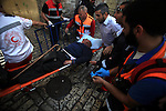 """Palestinian Medics carry a wounded during clashes outside the Al Aqsa mosque compound in the Old City of Jerusalem on April 16, 2014. Dozens of Palestinians were wounded in clashes with Israeli police that erupted when Jerusalem's flashpoint Al-Aqsa mosque compound which was opened to Jewish visitors. Palestinians threw """"stones and firecrackers"""" at police when they opened the walled compound's gates and Israeli police responded with stun grenades and rubber-coated bullets, they closed the complex to the Jewish visitors after a small number had toured the site. Photo by Saeed Qaq"""
