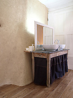 In the bathroom the walls have been finished in a natural lime plaster and the sink unit has been converted from an antique table