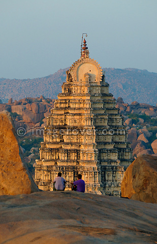 Tourists enjoying the view from Hemakuta Hill onto Virupaksha Temple at sunset in Hampi, Karnataka, India.