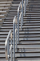 Stadium stairs abstract.   Straight horizonal lines bisected by curved hand rails climbing up, up, up.