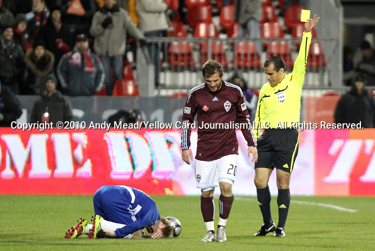 21 November 2010: Referee Baldomero Toledo (right) shows a yellow card to Colorado's Jamie Smith (SCO) (20) for a foul against Dallas' Dax McCarty (left). The Colorado Rapids defeated FC Dallas 2-1 in overtime at BMO Field in Toronto, Ontario, Canada in MLS Cup 2010, Major League Soccer's championship game.
