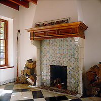 in the entrance hall the large fireplace is faced with antique blue-and-white ceramic tiles in contrast to a black-and-white marble floor laid in a diagonal pattern