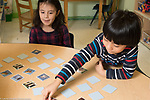 Education Preschool 4-5 year olds boy and girl playing memory game, taking turns to turn over matching cards