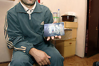 Chechen Man with a picture of his house in Grozny, destroyed by Russian bombing in 1999..He succeed to survive during 10 years of Chechen war, but in September 2005 the raids of dressed in cowl policemen or soldiers of Russian forces  visiting him at his place, threating him and his family life, put him to flight. They arrived in URiC Wola Center in Warsaw in the middle October..-For security reason, the face of the adult asylum seeker have been evicted of the photography..-For security reason, the names of the adult asylum seeker have been change. .-Article 9 of the Act of 13 June 2003 on grating protection on the Polish territory (Journal of Laws, No 128, it. 1176) personal data of refugees are an object of particular protection..-Cases where publication of a picture or name of asylum seeker had dramatic consequences for this persons and is family back in Chechnya. .Please have safety of those people in mind. Thank you.