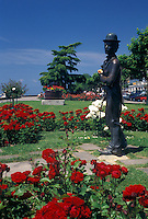 Switzerland, Vevey, Charlie Chaplin, Lake Geneva, Vaud, Statue of Charlie Chaplin holding a pink rose at the lakefront park along Lac Leman in Vevey in the Canton of Vaud. He is surrounded by beautiful red and white flowers.