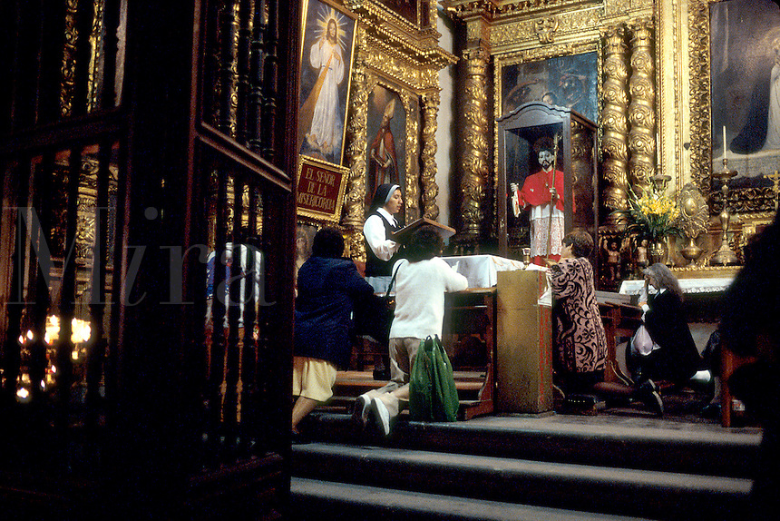 A nun gives a sermon as worshippers kneel in a small chapel in the Metorpolitan Cathedral. Mexico City.