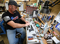 Burton Chaney, a gunsmith at Wilson Combat in Berryville, disassembles a Sig Sauer handgun Wednesday, March 4, 2020, at Wilson Combat in Berryville. Wilson Combat is working with Sig Sauer to provide custom work on two of the company's most popular handguns. Visit nwaonline.com/200308Daily/ for today's photo gallery.<br /> (NWA Democrat-Gazette/Andy Shupe)
