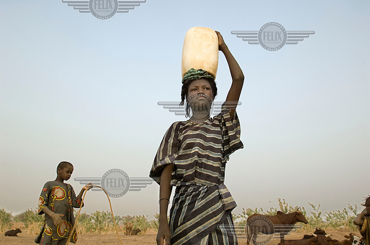 A girl carries water on her head in the village of Intedeyne.