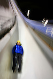 USA, Utah, Park City, Henry Druce races around turn 12 on his luge sled, Utah Olympic Park