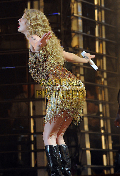 Taylor Swift.2011 CMA Music Festival Nightly Concert held at LP Field, Nashville, Tennessee, USA..June 12th, 2011.stage concert live gig performance music half length gold dress tassels fringed dress side 3/4 side profile bow bowing .CAP/ADM/LF.©Laura Farr/AdMedia/Capital Pictures.