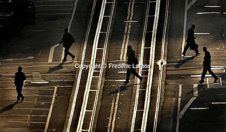 A group of early morning pedestrians pound the pavement crossing California Street in San Francisco, California.