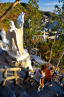 People walking down from the summit of Nui Lon (Big Mountain) to Bai Dau beach, past reiligious (Christian) statues, including the Virgin Mary and Baby Jesus Statue. Our Lady of Bai Dau Shrine, on Nui Lon (Big Mountain), Vung Tau, Vietnam.