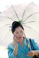Elegant Hmong woman under white sun umbrella speaking on cell phone. Hmong Sports Festival McMurray Field St Paul Minnesota USA