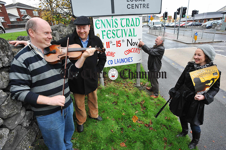 Musician and committee member Kevin Finucane plays a tune for hardworking fellow committee members; John Rynne, and Mike Butler, festival directors and Lorraine Battersby, while they erect signs on the approach to Ennis Town Centre for the Ennis Trad Festival which runs from the 11th to 15th November. Photograph by John Kelly.
