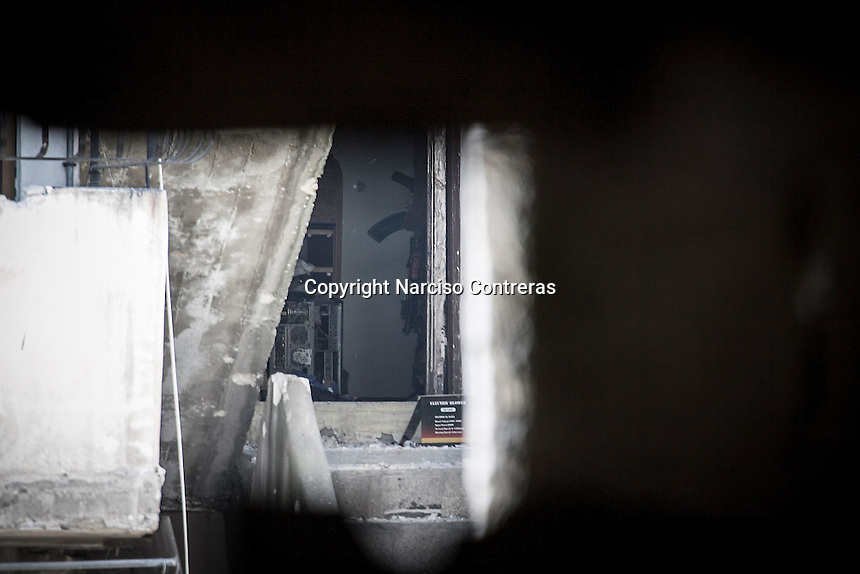 A Syrian army soldier is seen from a rebel sniper position at Salahadeen front line after several days of intense fighting between opposition fighters and troops loyal to president Bashar Al-Assad in the northern Syrian city of Aleppo.