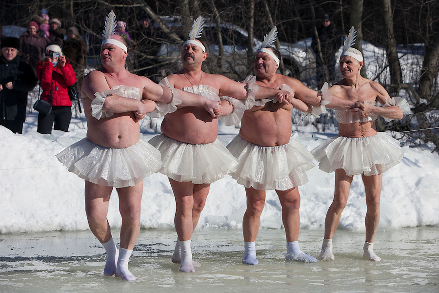 Moscow, Russia, 08/03/2010..Men of the Moscow Ice Swimming Club perform a routine from Swan Lake before swimming in a frozen lake during International Women's Day in northern Moscow. The club always hold their end of season party on Women's Day.
