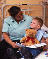 A nurse reads a story to her young patient in a hospital children's ward.  Date: 31.10.2005. <br />