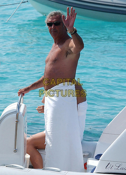 Flavio Briatore  .On vacation on their yacht off Sardinia , Italy..July 9th, 2003.half length couple vacation holiday sun water sunglasses shades white towel hand arm waving side .CAP/PPG.©People Picture/Capital Pictures