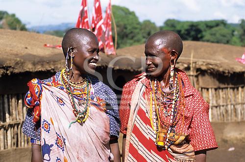 Lolgorian, Kenya. Siria Maasai Manyatta; two smiling woman, traditional beadwork earrings, decorations, extended ear piercing.