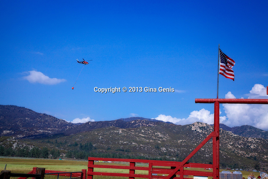 A helicopter flies near American flag as it returns to staging area during Mountain Center fire