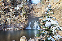 """Running Eagle Falls, This waterfall seems to pour out of the face of the rock, rather than over the top of it.  The falls is also known as """"Trick Falls"""" because in the spring, when more water is flowing, the creek cascades over the top of the hillside."""