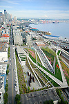 Aerial view looking south along the Seattle waterfront at the Olympic Sculpture Park.  Richard Serra's 'Wake' is the 5-piece sculpture at center bottom and Alexander Calder's 'Eagle' is the bright red piece in the lower right.  Downtown Seattle is in the back left, Elliott Bay is to the right with the orange cargo cranes of the Port of Seattle, and Mt. Rainier is in the distance.