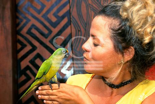Altamira, Brazil. Woman with green parakeet.