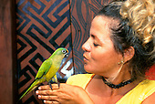 Altamira, Brazil. Woman with green parakeet.
