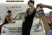 Chinese models pose besides a car of Shanghai Wanfeng Auto at the Auto China 2004 exhibition in Beijing, China..