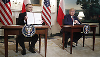 US President Donald J. Trump (R) and Polish President Andrzej Duda (L) participate in a signing ceremony in the Diplomatic Reception Room of the White House in Washington, DC, USA, 12 June 2019. President Trump and President Duda signed an agreement to increase military to military cooperation including the purchase of F-35 fighter jets by Poland and an increased US troop presence in Poland. <br /> Credit: Shawn Thew / Pool via CNP/AdMedia