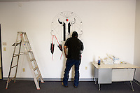 Artist Les White Antelope puts the finishing touches on a symbolic mural at the inauguration of a new language immersion school on the Wind River Indian Reservation in central Wyoming, Friday, Oct. 3, 2008. Northern Arapaho tribal leaders hope the inauguration of the larger new Arapaho Language Lodge immersion school at the reservation will help kids find a better cultural identity and strengthen them better succeed in education. (Kevin Moloney for the New York Times)