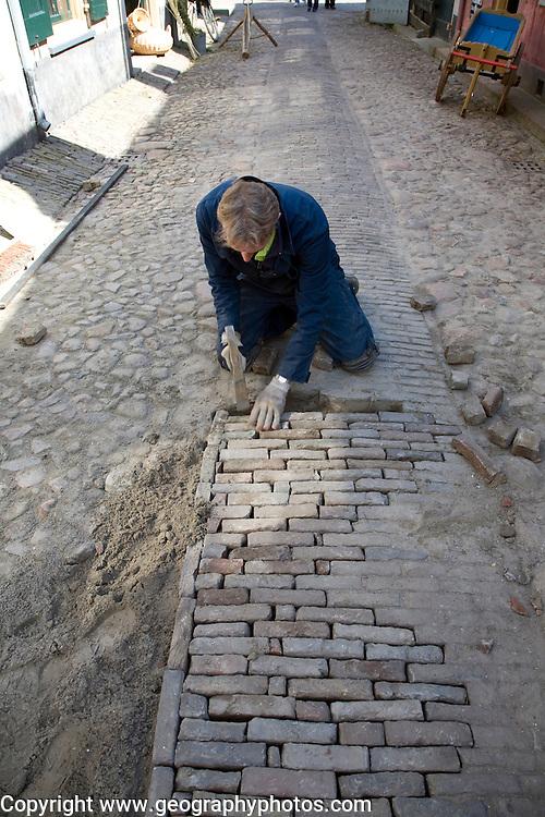 Man repairing cobbled street, Zuiderzee museum, Enkhuizen, Netherlands