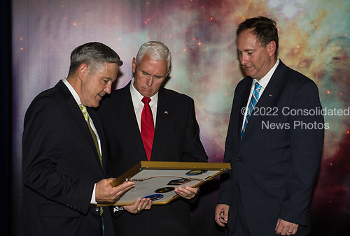 In this photo released by the National Aeronautics and Space Administration (NASA) United States Vice President Mike Pence receives a commemorative montage including an Indiana flag, representing the Vice President's hometown, that was flown in space, from NASA's Kennedy Space Center (KSC) Director, Robert Cabana, left, and Acting NASA Administrator, Robert Lightfoot, right, Thursday, July 6, 2017, in the green room at NASA&rsquo;s Kennedy Space Center (KSC) in Cape Canaveral, Florida. Vice President Mike Pence is scheduled to speak at the event to highlight innovations made in America and tour some of the public/private partnership work that is helping to transform the center into a multi-user spaceport. <br /> Mandatory Credit: Aubrey Gemignani / NASA via CNP