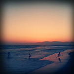 Kids play in the Pacific Ocean at sunset on the summer solstice in Venice Beach, California