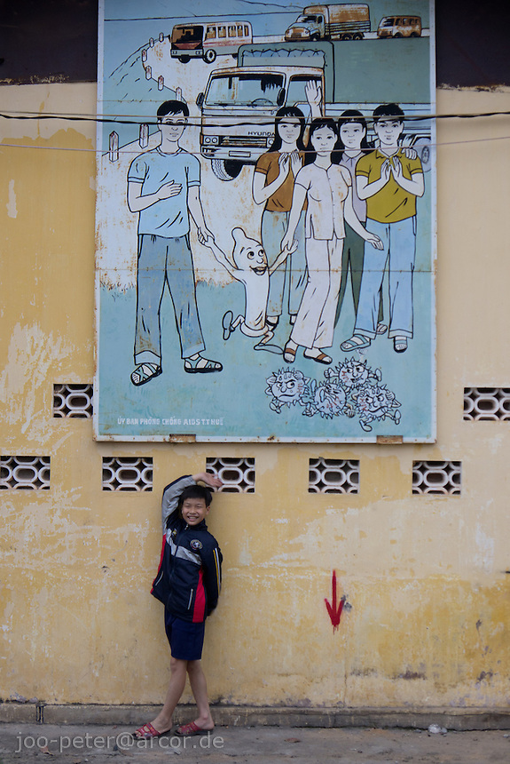 boy in  front of a billboard with paintings for aids prevention in city Hue, Vietnam