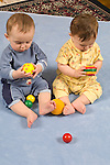 8 month old frateral twin baby boys sitting side by side each holding and examining small balls with both hands vertical Caucasian