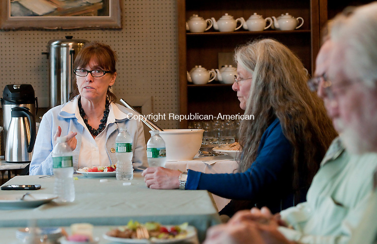 WATERBURY, CT--042215JS03- Edy Reynolds, left owner of John Bale Bookstore in Waterbury, welcomes local residents to dinner at the bookstore on Wednesday.  Volunteers and residents were invited to the event to talk about positive changes that could be implemented in the city of Waterbury. <br /> Jim Shannon Republican-American