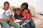 Family at home father and mother with sons ages 3, and 1 year old sitting on couch in living room looking at picture book, father reading horizontal