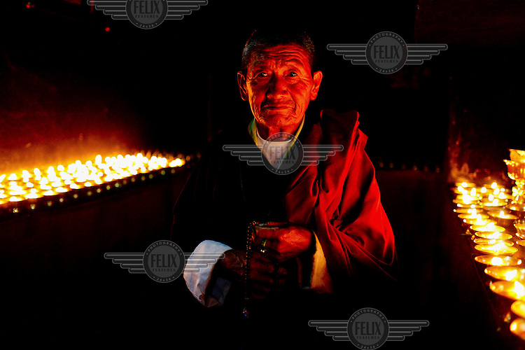A portrait of a monk standing by candles at a Buddhist monastery in Thimpu.