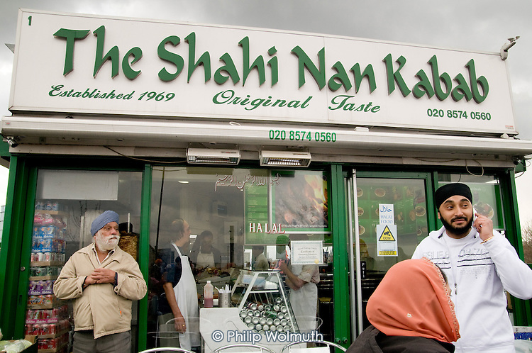 Bystanders outside a kebab shop in Southall, West London, watch as thousands of local residents join a procession to celebrate the Sikh festival of Vaisakhi.