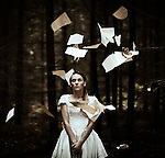 Woman standing in woodland wearing a white dress watching falling pages