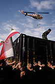 "Tehran, Iran .June 7, 1989..Hundreds of mourners visit and touch the tomb of the Grand Ayatullah Sayid Ruhullah Musawi Khomeini in the Beheht-E-Zahra cemetery the morning following his funeral. Flowers are dropped by helicopters from above and women have soldiers guarding the tomb, touch their babies to it's walls as a blessing. He died of heart attack on June 3, 1989...Khomeini was a senior Shi`i Muslim cleric, Islamic philosopher and marja (religious authority), and the political leader of the 1979 Iranian Revolution that saw the overthrow of Mohammad Reza Pahlavi, the last Shah of Iran. Following the revolution, Khomeini became the country's Supreme Leader?the paramount political figure of the new Islamic Republic...Khomeini was a marja al-taqlid, (source of imitation) and important spiritual leader to many Shia Muslims. He was also an innovative Islamic political theorist, most noted for his development of the theory of velayat-e faqih, the ""guardianship of the jurisconsult (clerical authority)"". He was named Time's Man of the Year in 1979 and also one of Time magazine's 100 most influential people of the 20th century."
